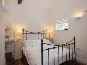 A bed or beds in a room at Millpool Cottage