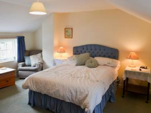 A bed or beds in a room at Watercolour Cottage
