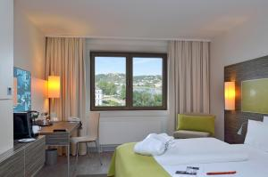 A bed or beds in a room at Mercure Hotel Koblenz