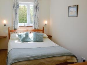 A bed or beds in a room at Rose Cottage IV