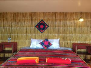 A bed or beds in a room at Uros Lodge Lago Titicaca Peru