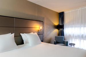 A bed or beds in a room at City Hotel Groningen
