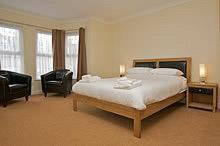 A bed or beds in a room at All Seasons Lodge Hotel