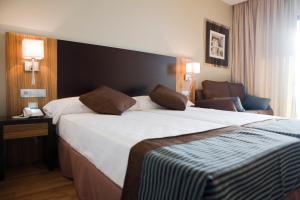 A bed or beds in a room at Hotel y Apartamentos Conilsol