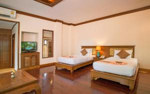 A bed or beds in a room at Sunrise Tropical Resort