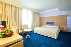 A bed or beds in a room at El Mouradi Mahdia