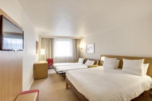 A bed or beds in a room at Novotel Paris Sud Porte de Charenton