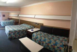 A bed or beds in a room at City Beach Motel