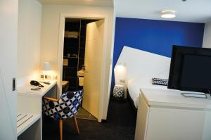 A television and/or entertainment centre at Hôtel ORIGAMI