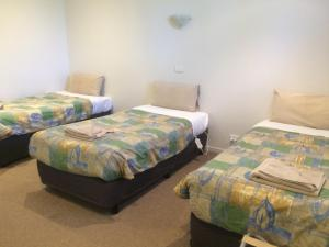 A bed or beds in a room at Ambassador Motor Inn