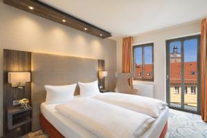 Een bed of bedden in een kamer bij Hotel Krämerbrücke Erfurt
