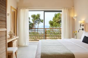 A bed or beds in a room at ELIVI Skiathos