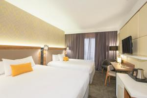 A bed or beds in a room at L'Elysée Val d'Europe