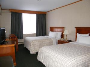 A bed or beds in a room at Travelodge Hotel by Wyndham Montreal Airport