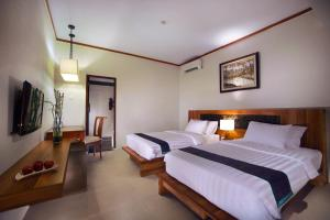 A bed or beds in a room at Aston Sunset Beach Resort - Gili Trawangan