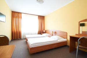A bed or beds in a room at Obiekt Hotelarski Patron