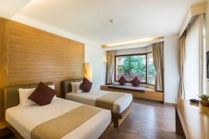 A bed or beds in a room at Ayrest Hua Hin Hotel