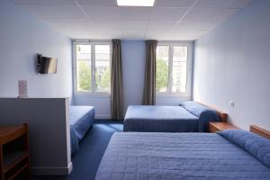 A bed or beds in a room at Hotel Le Petit Duquesne