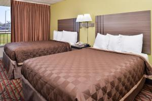 A bed or beds in a room at Americas Best Value Inn West Monroe