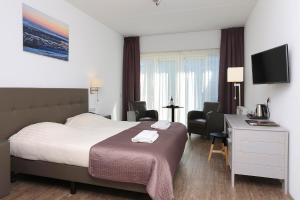 A bed or beds in a room at Hotel Cafe Restaurant Duinzicht