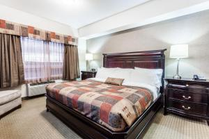 A bed or beds in a room at Ramada by Wyndham Westlock