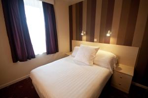 A bed or beds in a room at Norfolk Hotel
