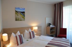 Een bed of bedden in een kamer bij Flair Hotel am Rosenhügel
