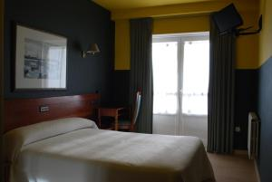 A bed or beds in a room at Hotel San Jacobo