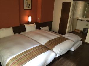 A bed or beds in a room at Kyomachiya Ryokan Sakura Hongan-G