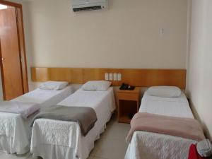 A bed or beds in a room at Hotel Sao Miguel