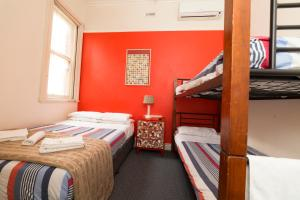 A bed or beds in a room at Tassie Backpackers at The Brunswick Hotel