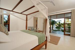 A bed or beds in a room at Kisiwa on the Beach