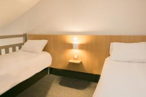 A bed or beds in a room at B&B Hôtel Alencon Nord