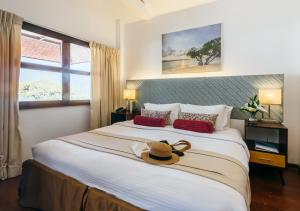 A bed or beds in a room at Club Paradise Resort Palawan