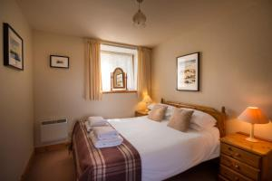 A bed or beds in a room at Carden Holiday Cottages - Elgin