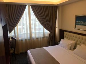 A bed or beds in a room at Golden Tulip Midtown