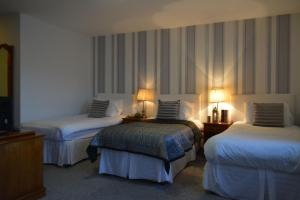 A bed or beds in a room at Woodfield House Hotel