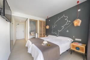 A bed or beds in a room at Hotel Playasol Cala Tarida