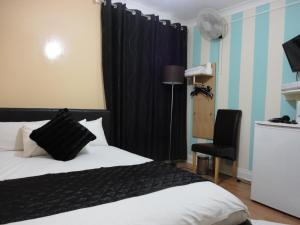 A bed or beds in a room at City View Hotel - Roman Road Market