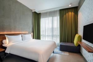 A bed or beds in a room at ibis Styles Kota Kinabalu Inanam
