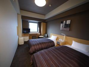 A bed or beds in a room at Route Inn Grantia Hakodate Ekimae