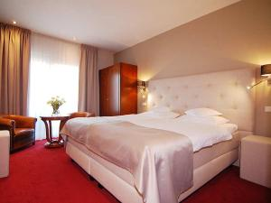 A bed or beds in a room at Romantik Parkhotel het Gulpdal