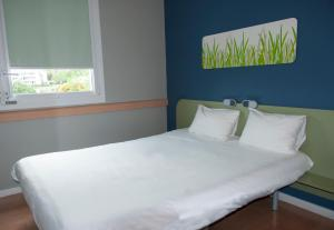 A bed or beds in a room at ibis budget Rodez
