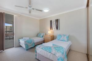 A bed or beds in a room at Beach Palms Holiday Apartments