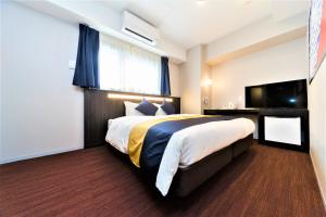 A bed or beds in a room at Kuromon Crystal Hotel