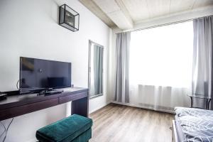Televízia a/alebo spoločenská miestnosť v ubytovaní HOTEL 63