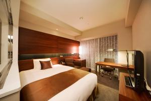 A bed or beds in a room at Hotel Metropolitan Akita