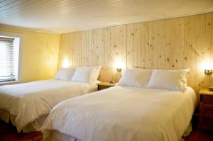 A bed or beds in a room at La Galouine auberge et Restaurant