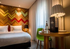 A bed or beds in a room at Cucu Hotel By 7Minds