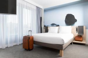 A bed or beds in a room at Novotel Charleroi Centre